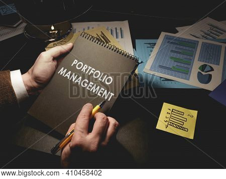 Man Makes Notes About Portfolio Management In The Notepad.