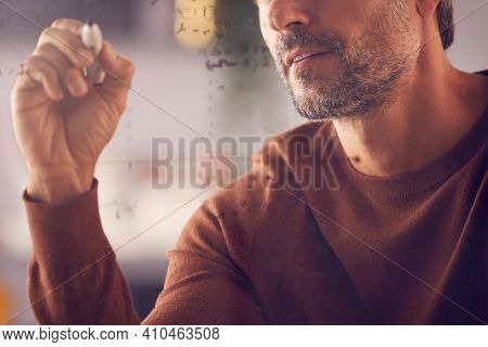 Close Up Of Businessman Or Mathematician Drawing Graph Calculation On Glass Screen In Office