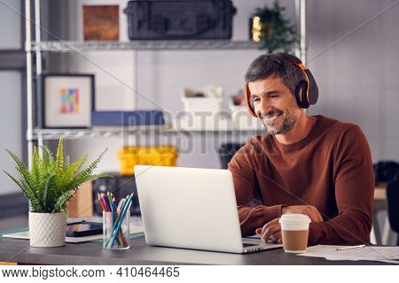 Male Advertising Marketing Or Design Creative With Wireless Headphones At Desk Working On Laptop