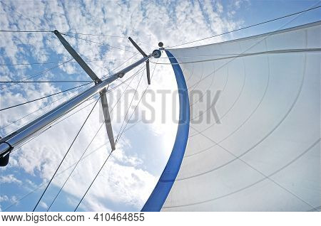 From Below Shot Of White Waving Sail On Tall Mast Under Blue Sky In Clouds . White Sail On Mast Unde