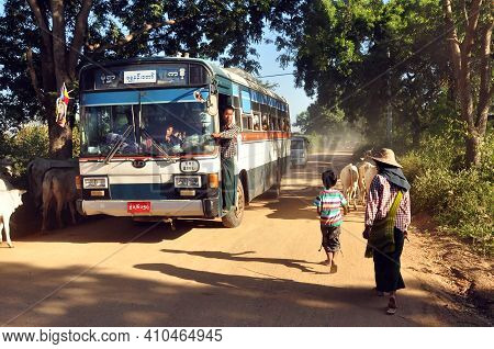Bagan, Myanmar - November 18, 2015: Bus On Rural Road In Village, View Of People And Cattle On Remot