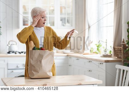 Amazed Elderly Woman With Paper Bag Full Of Food Checking Grocery Bill And Touching Her Head, Standi