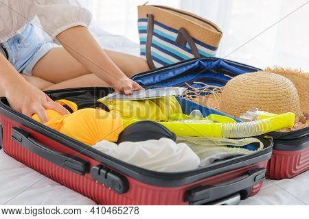 Close-up Female Hands Packing Summer Clothes And Beach Accessories Into Suitcases On Bed. Preparing