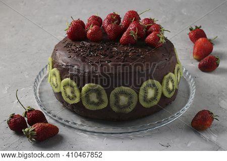 Chocolate Homemade Cake Decorated Strawberries And Kiwi Located On Gray Concrete Background, Horizon