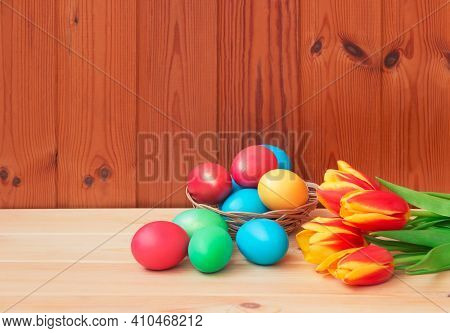 Colorful Easter Eggs In Wicker Basket And Tulip Flowers On Wooden Background. Selective Focus. View