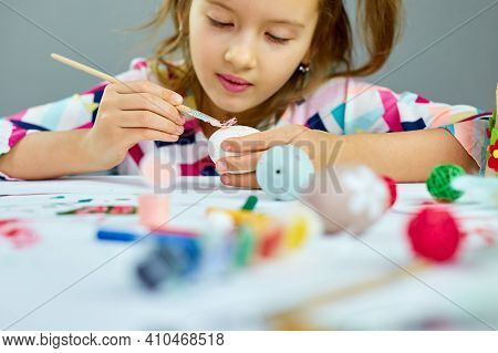 Happy Little Girl Painting, Drawing With Brush Eggs At Home.