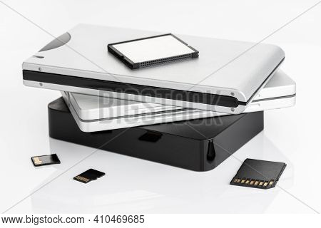 Group Of External Hard Disks And Memory Cards On White Table. Data Storage Concept