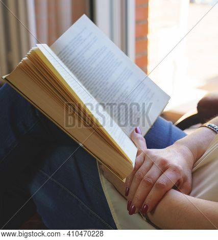 White Woman Reading A Book In An Armchair Relaxing In Nice Daylight Outside. Copy Space. Reading, Te