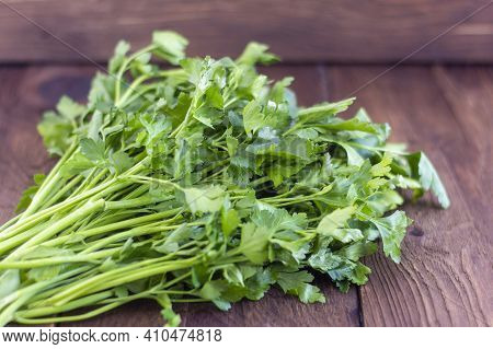 A Bunch Of Parsley On A Wooden Background. Organic Parsley Close-up On A Rustic Board. A Bunch Of Ra