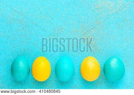 Glam Easter Composition. Colorful Easter Eggs In A Row And Glitter On Pastel Cyan Background. Top Vi