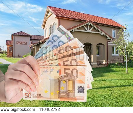 Modern Cottage On A Lawn. Purchase, Sale, Rent Of A Cottage. Hand With  Foreign Banknotes In The For
