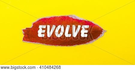 On A Yellow Background, A Sheet Of Red Paper With The Word Evolve