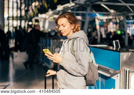 Young Attractive Caucasian Woman At The Airport Waiting For Departure And Watching Social Media On T