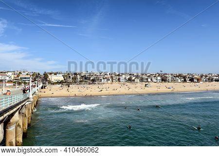 MANHATTAN BEACH, CALIFORNIA - 17 FEB 2020: Manhattan Beach Pier looking towards the beach with surfers, sunbathers and homes.