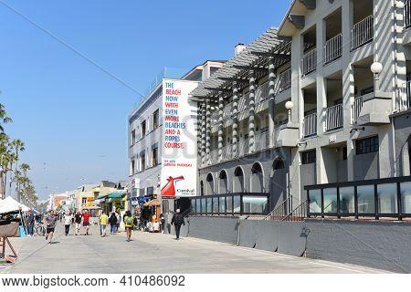VENICE, CALIFORNIA - 17 FEB 2020: Shops along the Venice Beach Boardwalk with, tourists and sidewalk vendors.