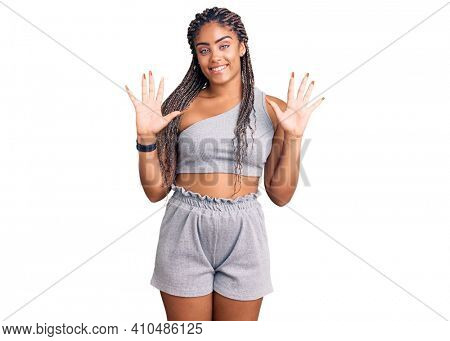 Young african american woman with braids wearing sportswear showing and pointing up with fingers number ten while smiling confident and happy.