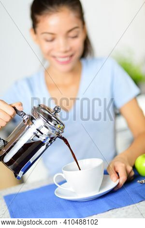 Coffee - woman drinking french press coffee at breakfast table in the morning. Girl pouring black coffee at home in kitchen.