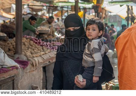 Jaipur, India. 09-05-2018. Muslim Woman With Wail Dress In Black Carrying Her Child Is Walking In Th