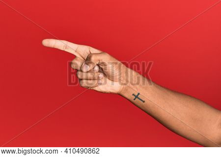 Hand of hispanic man over red isolated background pointing with index finger to the side, suggesting and selecting a choice