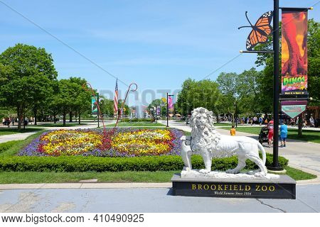 BROOKFIELD, ILLINOIS - MAY 27, 2017: Lion Statue at the Brookfield Zoo South Gate. Roosevelt Fountain and the Carousel are in the background