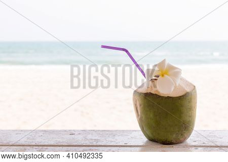 Coconut On Wooden Floor With Sea Background. Tropical Fresh Coconut Cocktail Decorated Plumeria On W