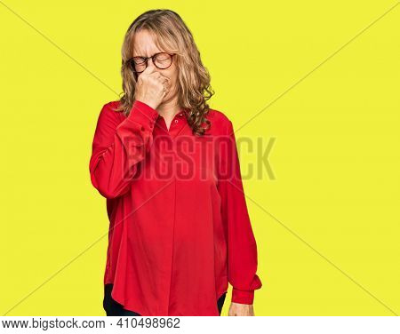 Middle age blonde woman wearing casual shirt over red background smelling something stinky and disgusting, intolerable smell, holding breath with fingers on nose. bad smell