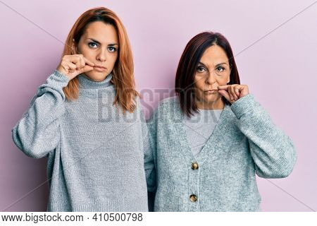 Latin mother and daughter wearing casual clothes mouth and lips shut as zip with fingers. secret and silent, taboo talking