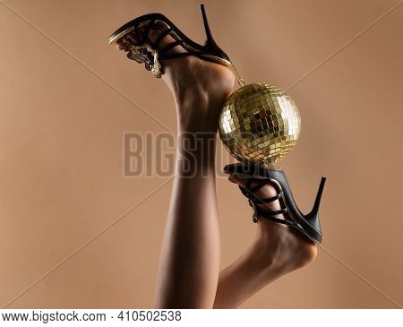 Sexy Woman Legs. Disco Party Event. Woman High Heels With Gold Disco Ball. Celebrating Background