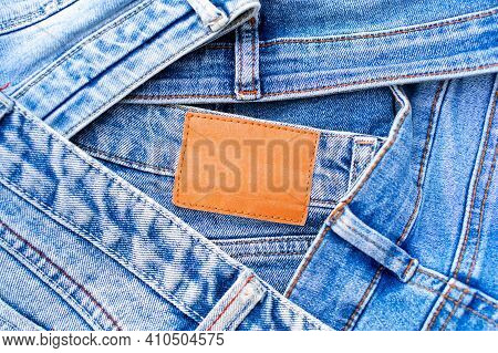 Denim Texture, Pile Of Blue Jeans And Blank Leather Label Close Up, Variety Of Comfortable Casual Pa