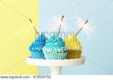 Celebration cupcakes decorated with blue and yellow frosting and sparklers for a birthday party