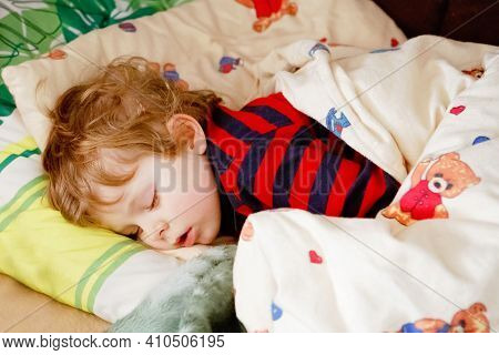Adorable Little Blond Kid Boy In Colorful Nightwear Clothes Sleeping And Dreaming In His Bed. Health