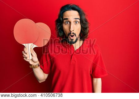 Young hispanic man holding red ping pong rackets scared and amazed with open mouth for surprise, disbelief face