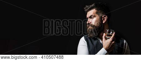 Man Drinking Whiskey, Brandy, Cognac. Degustation, Tasting. Man With Beard Holds Glass Of Brandy. Ta