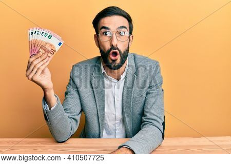 Young hispanic man holding euro banknotes scared and amazed with open mouth for surprise, disbelief face