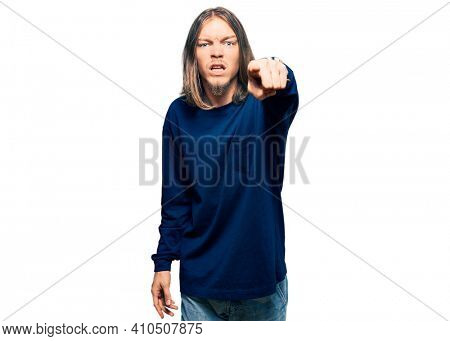 Handsome caucasian man with long hair wearing casual winter sweater pointing displeased and frustrated to the camera, angry and furious with you