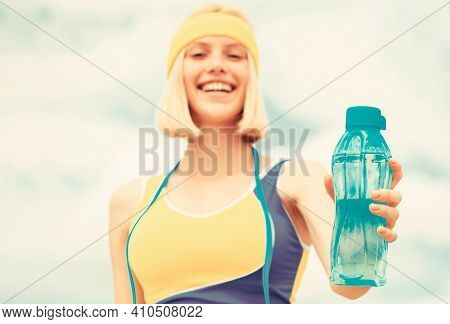 Sports Girl Drinks Water From A Bottle On A Sky Background. Drinking During Sport. Woman In Sportswe