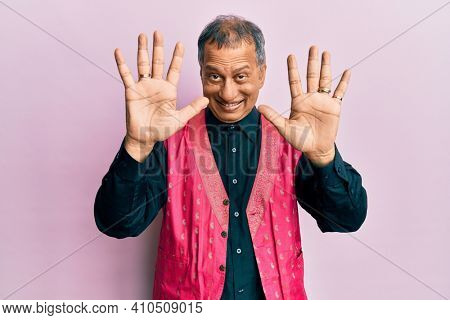 Middle age indian man wearing traditional indian clothes showing and pointing up with fingers number ten while smiling confident and happy.
