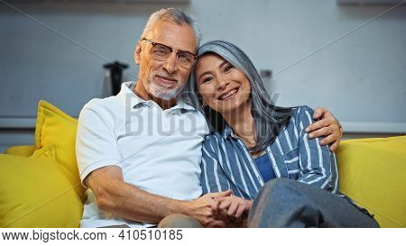 Cheerful Elderly Interracial Couple Smiling At Camera While Hugging On Sofa At Home
