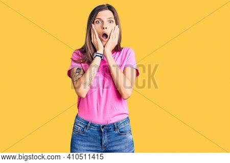 Beautiful caucasian woman wearing casual clothes afraid and shocked, surprise and amazed expression with hands on face