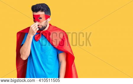 Young handsome man with beard wearing super hero costume smelling something stinky and disgusting, intolerable smell, holding breath with fingers on nose. bad smell