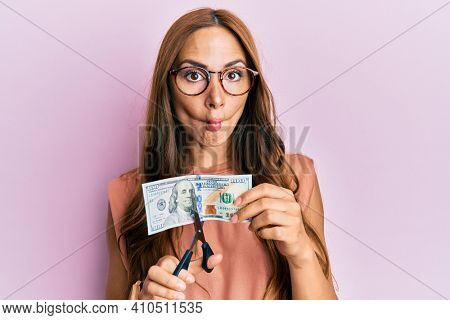 Young brunette woman cutting dollars with scissors for currency devaluation making fish face with mouth and squinting eyes, crazy and comical.