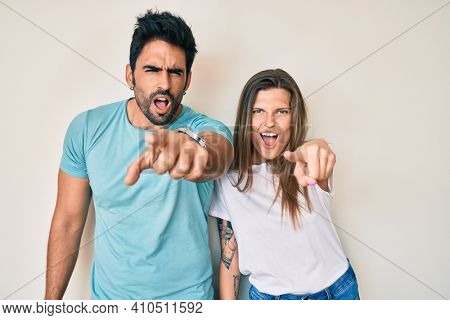 Beautiful young couple of boyfriend and girlfriend together pointing displeased and frustrated to the camera, angry and furious with you