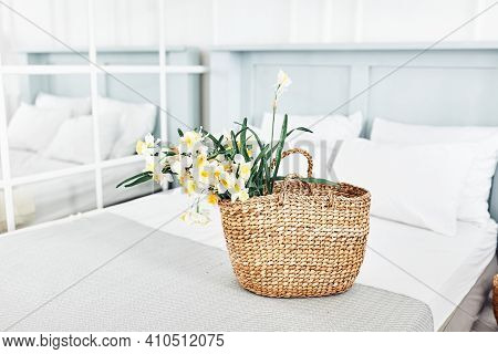 Many Yellow Spring Daffodils In Wicker Basket For Easter Holiday Decor In Cozy Scandinavian Bedroom.