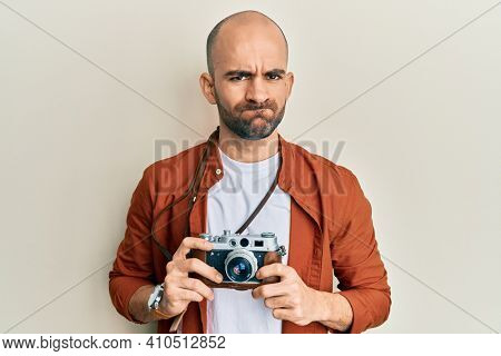 Young hispanic man holding vintage camera skeptic and nervous, frowning upset because of problem. negative person.