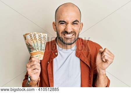 Young hispanic man holding 500 norwegian krone banknotes screaming proud, celebrating victory and success very excited with raised arm