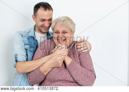 Head Shot Happy Young Bearded Man Embracing Beautiful Smiling Middle Aged Senior Mother In Eyewear,