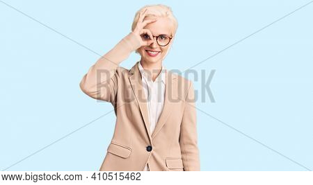 Young blonde woman wearing business clothes and glasses doing ok gesture with hand smiling, eye looking through fingers with happy face.