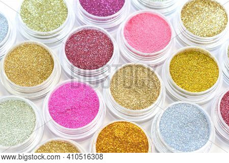 Gold And Pink Glitter In Jars On A White Background. Shiny Powder, Pigments, Sparkle. Beautiful Shim