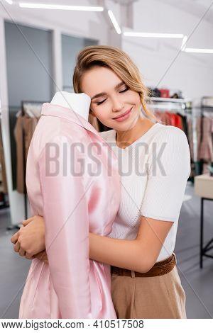 Smiling Seller Of Showroom Hugging Pink Coat On Mannequin