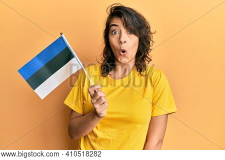 Young hispanic woman holding estonia flag scared and amazed with open mouth for surprise, disbelief face